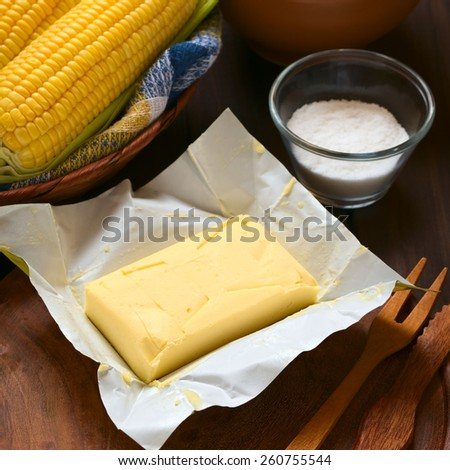 Piece of butter with salt and cooked sweetcorn photographed on wood with natural light (Selective Focus, Focus on the front of the butter) - stock photo