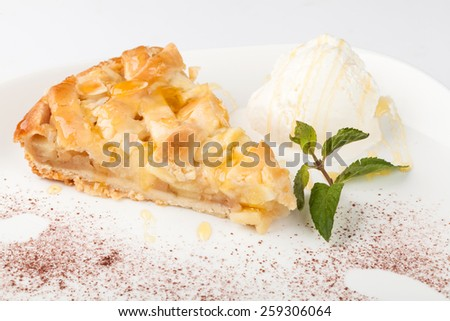 Piece of cake charlotte with apples ice cream and fresh mint on a white plate - stock photo