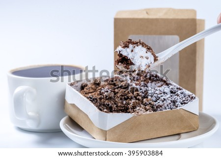 piece of cake on a spoon close-up on a background of coffee cups - stock photo