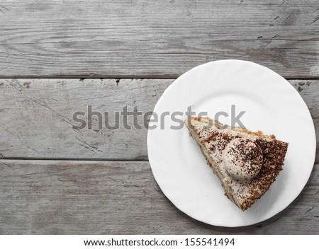 Piece of cake on the wooden table, top view, space for text - stock photo