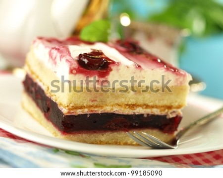 Piece of cake with cherries and whipped cream
