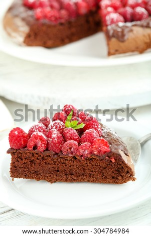 Piece of cake with chocolate Glaze and raspberries on color wooden background