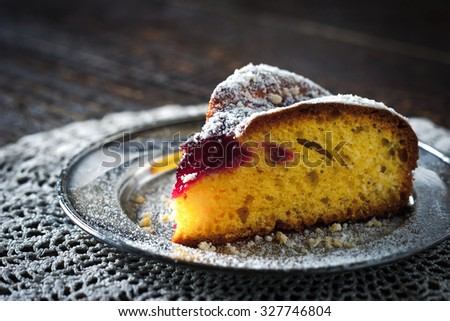 Piece of cake with icing sugar and jam on the lace napkin close - up