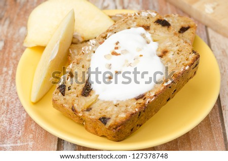 piece of cake with oatmeal, quince and prunes on a yellow plate, horizontal closeup - stock photo