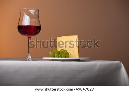 piece of cheese,a bunch of grapes and red wine