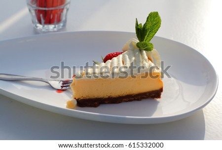 Piece of cheese cake with whipped cream and strawberry and mint on the plate on white cafe table