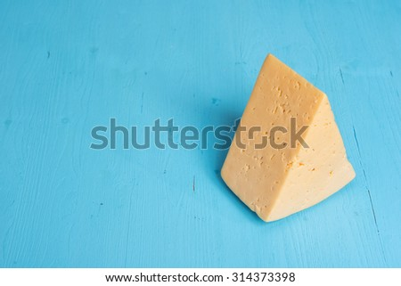 piece of cheese on a blue wooden background - stock photo