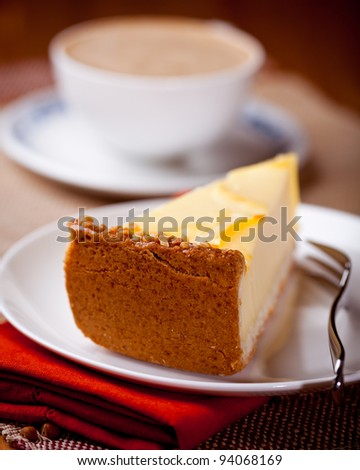 Piece of cheesecake and a cup of cappuccino in background