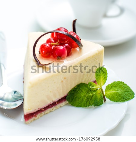 piece of cheesecake decorated with currant and spoon - stock photo