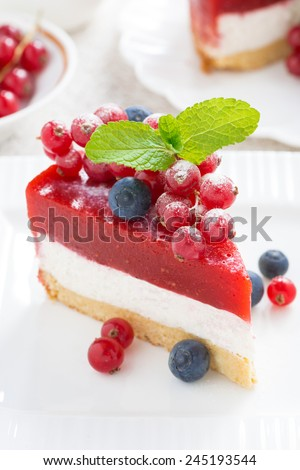 piece of cheesecake with berry jelly on a white plate, close-up, vertical - stock photo