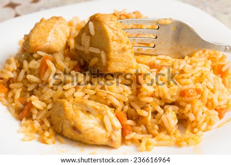 Piece of chicken impaled on a fork on a plate with pilaf