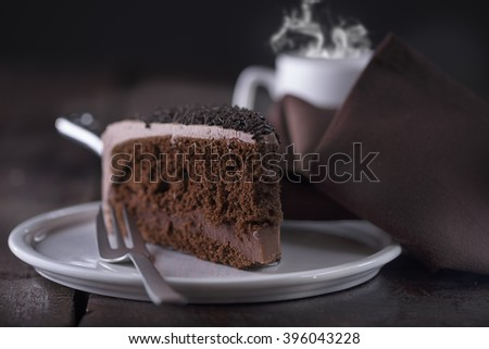 Piece of chocolate cake and a fork on the left side. A cup of hot coffee with steam in the background. View from Left Front - stock photo
