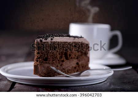 Piece of chocolate cake and a fork on the right side. A Cup of hot coffee with steam in the background. View from right Front