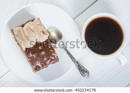 piece of chocolate cake and cup of coffee on a background of white painted wood
