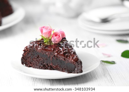 Piece of chocolate cake decorated with flowers on white wooden table - stock photo