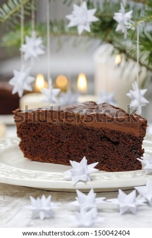 Piece of chocolate cake in white christmas table setting. Very selective and soft focus.