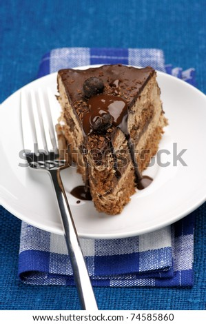 Piece of chocolate cake in white plate on blue background.