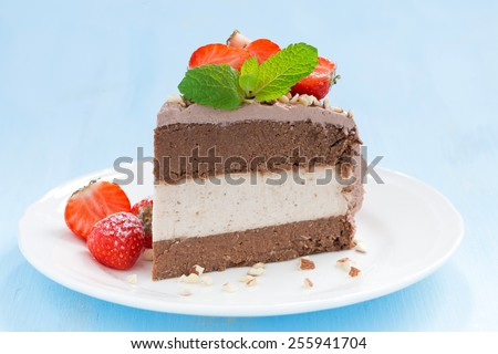 piece of chocolate cake of three layers, close-up - stock photo