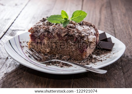 Piece of Chocolate Cake on a plate on wooden background - stock photo