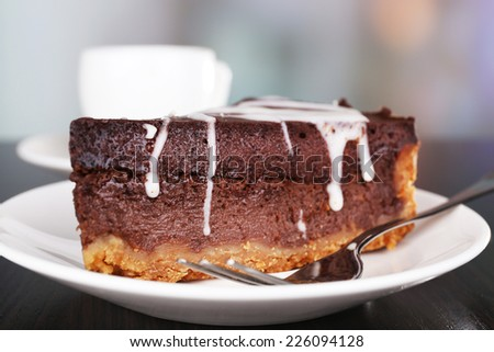 Piece of chocolate cake on plate and cup of tea on wooden table on natural background - stock photo