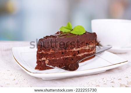 Piece of chocolate cake on plate on lace napkin and cup of tea on wooden table on natural background - stock photo