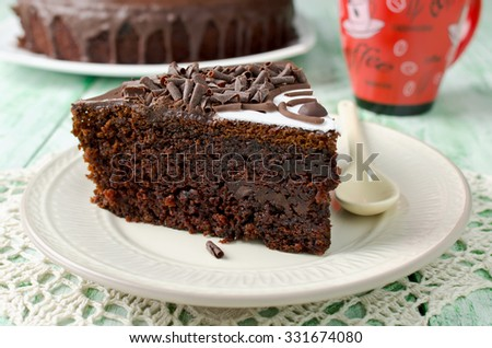 Piece of chocolate cake with banana. Cake decorated with mastic and chocolate chips - stock photo