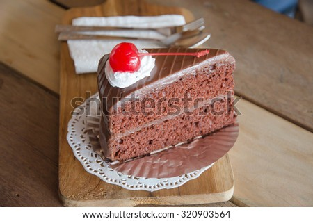 piece of chocolate cake with chocolate mousse layer and cherry on top. Delicious chocolate cake on plate on wooden table.