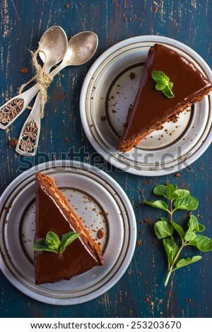 piece of chocolate cake with mint leaves, top view - stock photo