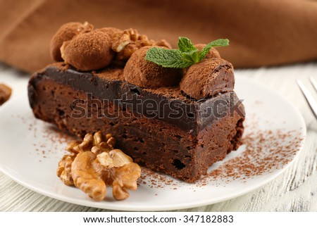 Piece of chocolate cake with walnut and mint on the table, close-up