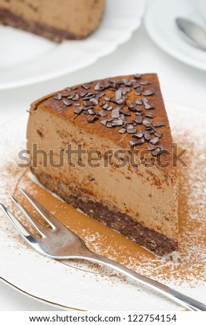piece of chocolate cheesecake sprinkled with cocoa on a white plate, top view - stock photo