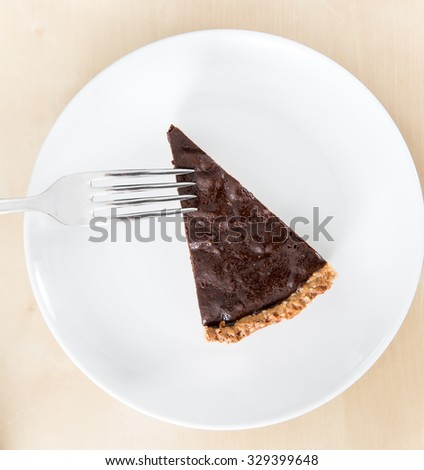 Piece of chocolate tart or pie on a white ceramic dish with stainless steel fork (top view)