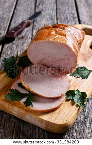 Piece of cooked ham on a wooden surface. Selective focus. - stock photo
