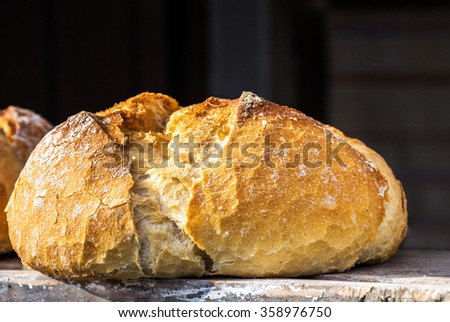 Piece of crispy bread over wood table - stock photo