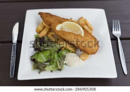 Piece of crumbed fish placed on top of chips with a slice of lemon on top. Garden salad and tartar sauce on side. Square plate on outdoor wooden table.  - stock photo