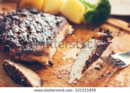 piece of cut well done pork chop with fork - stock photo