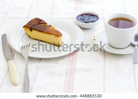Piece of delicious cottage cheese casserole with jam on a plate and a cup of tea for breakfast