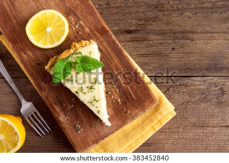 Piece of delicious homemade lemon cheesecake with mint on rustic wooden background with copy space - stock photo