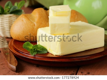 piece of fresh butter for breakfast on a wooden board