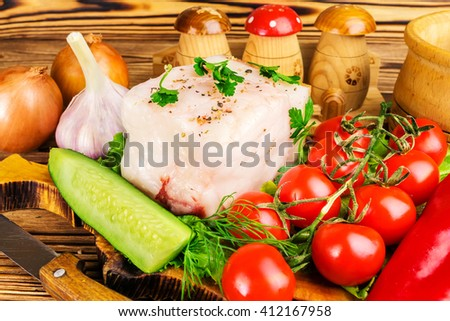 Piece of fresh pork lard, fresh produce, greens, vegetables on the wooden board and knife on table, close-up, selective focus. - stock photo