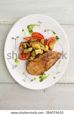 Piece of fried chicken with vegetables: zucchini, tomatoes, mushrooms with pesto and herbs, served on a white plate on a wooden background - stock photo