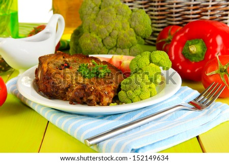 Piece of fried meat on plate on wooden table close-up - stock photo