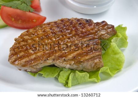Piece of fried meat with vegetables on a white plate.