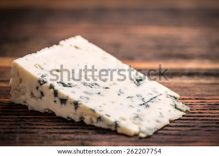 Piece of gorgonzola cheese on wooden board - stock photo