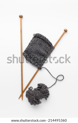 Piece of grey knitting on knitting needles - stock photo
