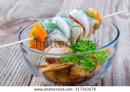 Piece of herring, sweet pepper, and onion on a stick on a glass bowl with fried potato slices on a wooden table.