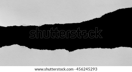 Piece of hole paper on black. Copy space