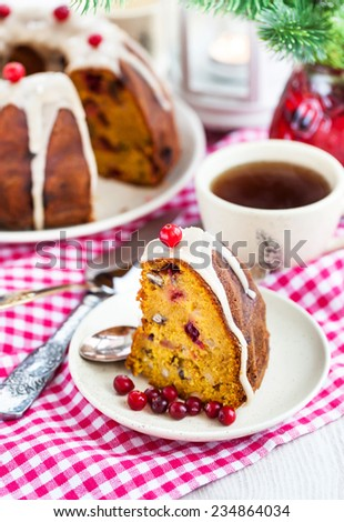 Piece of holiday bundt cake decorated with icing and cranberr - stock photo
