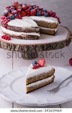 Piece of home made Earl Grey cake with cream cheese and berries and mashed strawberries in brandy inside, with strawberry, red currant and blueberries - stock photo