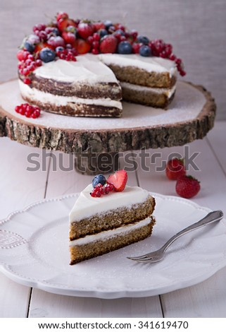 Piece of home made Earl Grey cake with cream cheese and berries and mashed strawberries in brandy inside, on white plate with strawberry, red currant and blueberry - stock photo