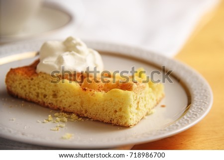 piece of homemade apple cake with whipped cream on a white plate, close up, copy space, selected focus, very narrow depth of field